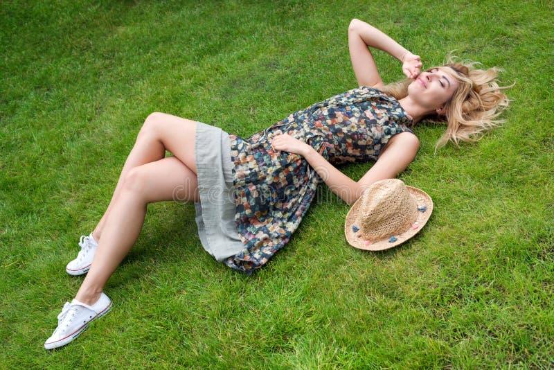 Ung kvinna som kopplar av på en härlig grön äng arkivfoto