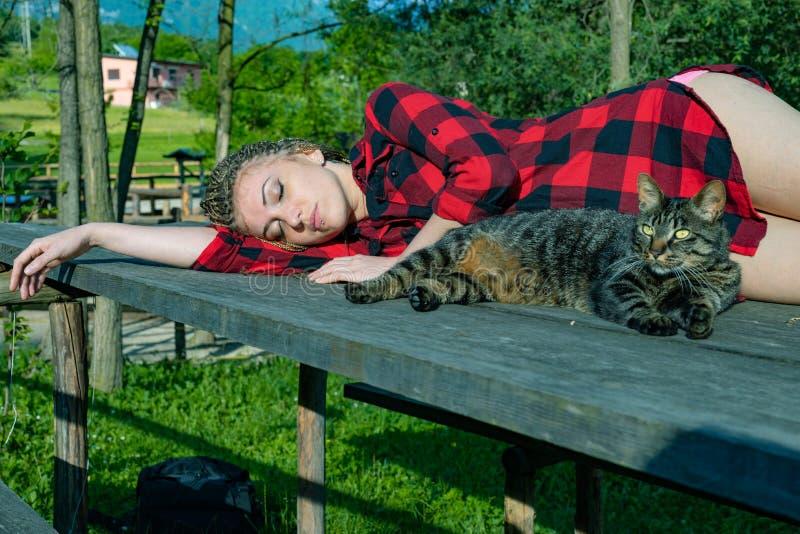 Ung kvinna som kopplar av på en utomhus- tabell fotografering för bildbyråer