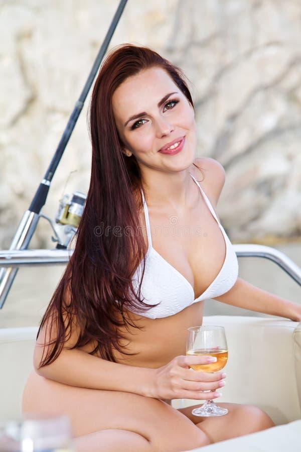 Ung kvinna som kopplar av på en yacht royaltyfri foto