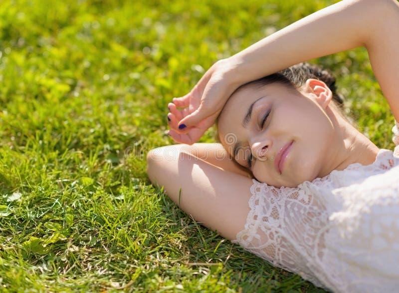 Ung kvinna som kopplar av på gräs arkivbild