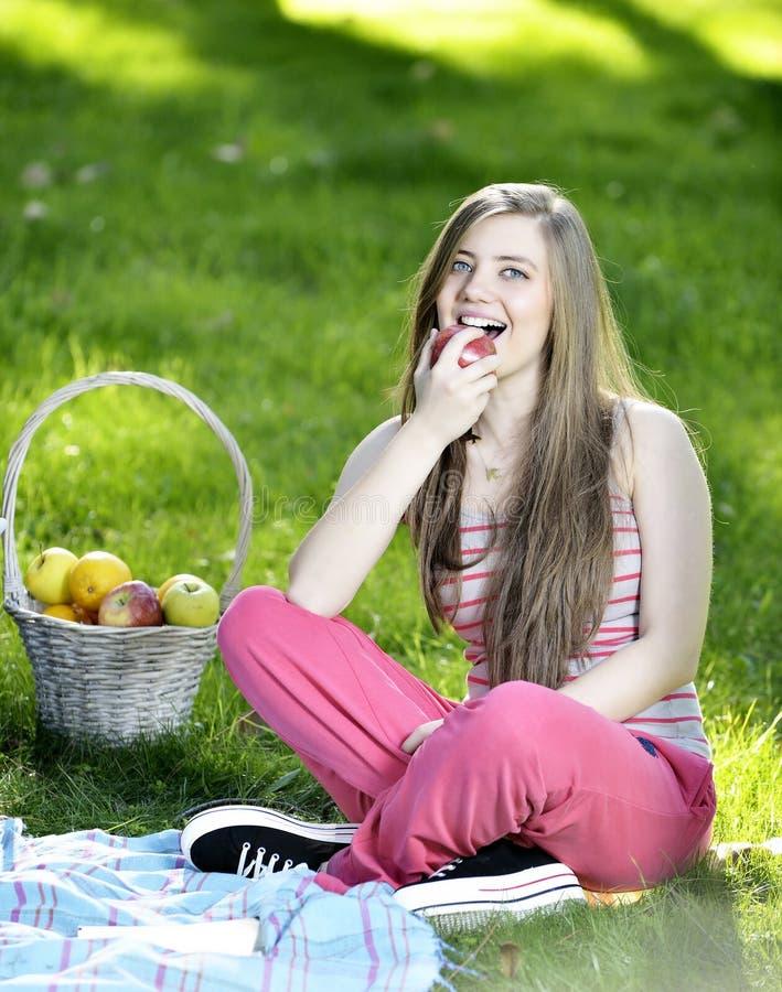 Ung kvinna som kopplar av på gräset och äter äpplen fotografering för bildbyråer