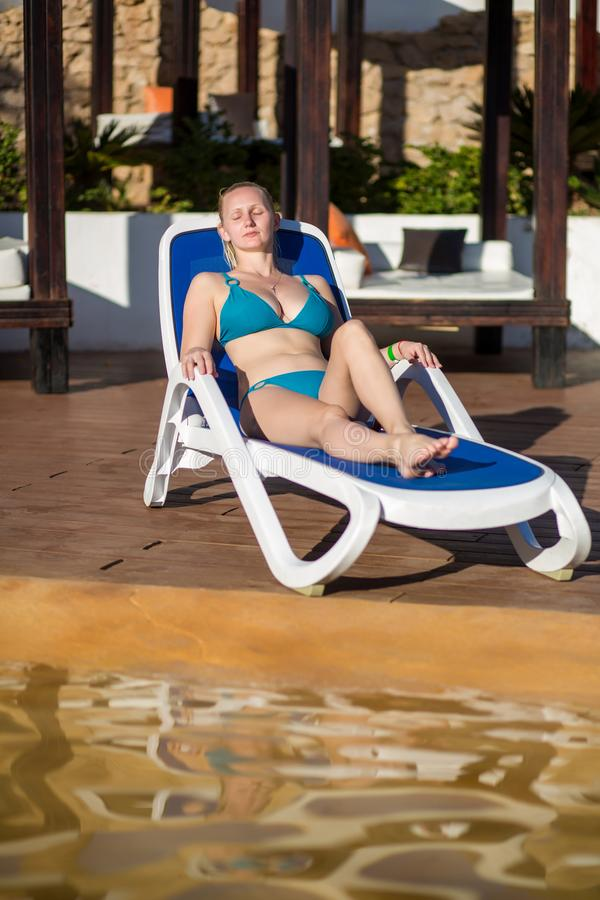 Ung kvinna som kopplar av på solstolen av simbassängen på semesterorten arkivfoto