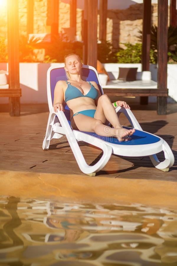 Ung kvinna som kopplar av på solstolen av simbassängen på semesterorten Solsignalljus fotografering för bildbyråer