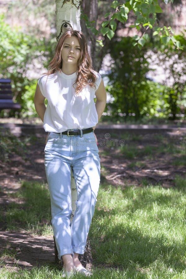 Ung kvinna som kramar björkträd V?r Soligt avmaska dagen, att tycka om som är utomhus- arkivfoton