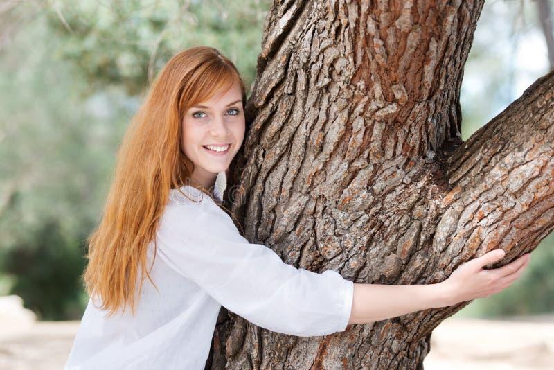 Ung kvinna som kramar ett träd royaltyfri bild