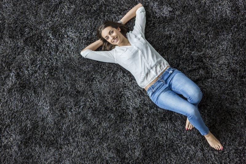 Ung kvinna som lägger på matta royaltyfri bild