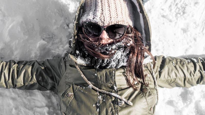 Ung kvinna som lägger på snö arkivbild