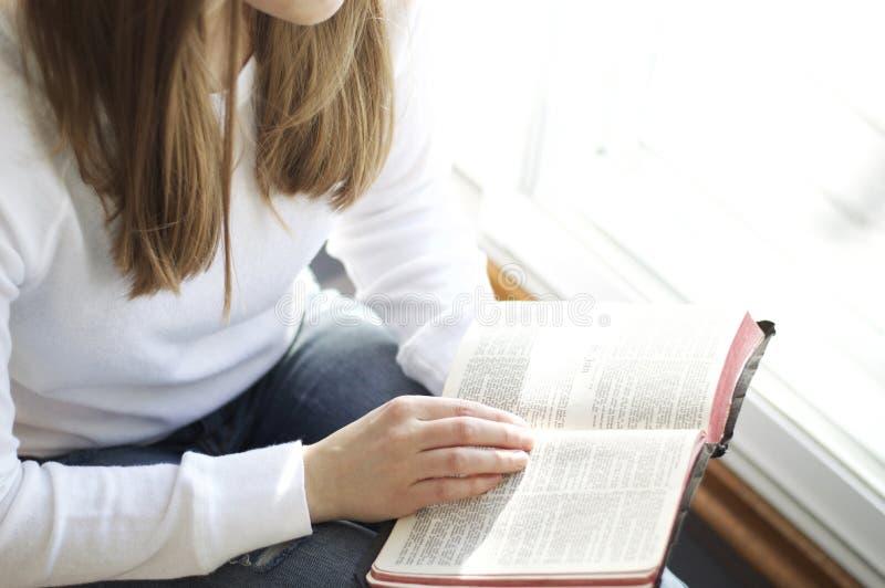 Ung kvinna som läser den heliga bibeln fotografering för bildbyråer