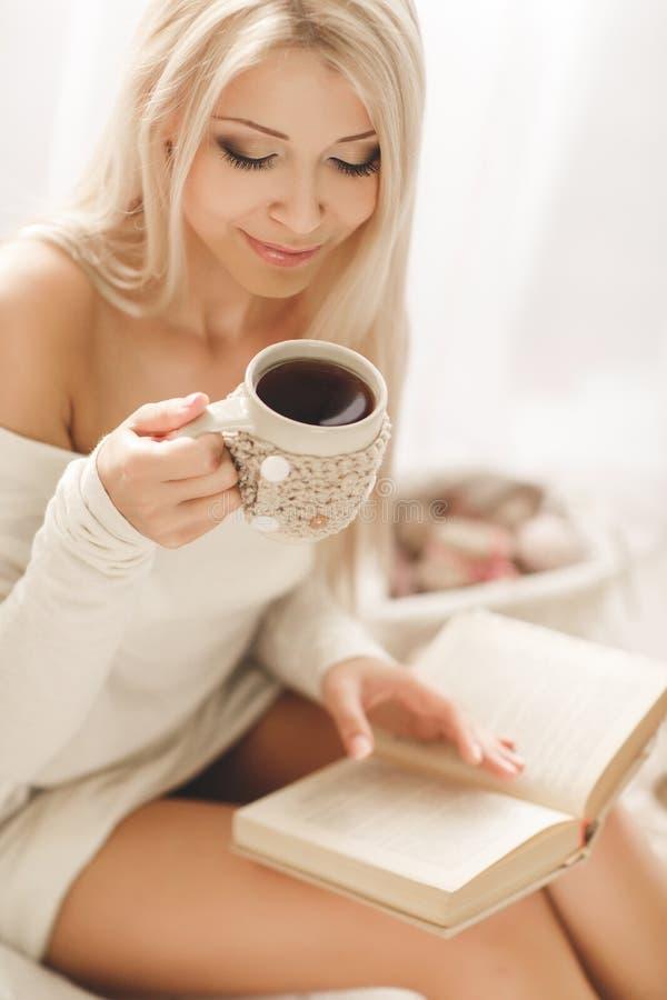Ung kvinna som läser en bok och dricker kaffe royaltyfri foto