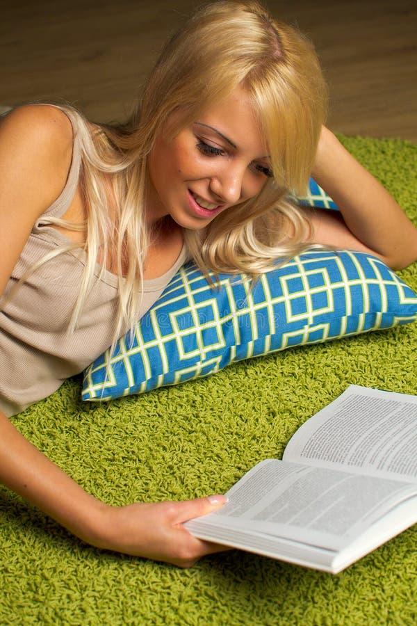 Ung kvinna som läser en bok på golvet arkivbild