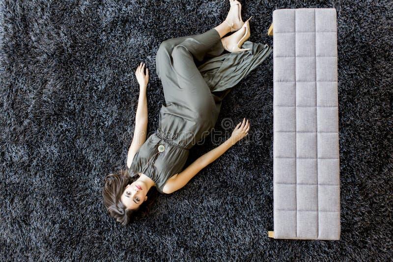 Ung kvinna som läser en bok på golvet royaltyfri foto