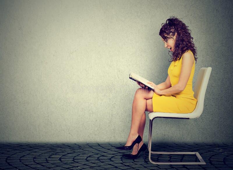 Ung kvinna som läser ett boksammanträde på en stol royaltyfri fotografi