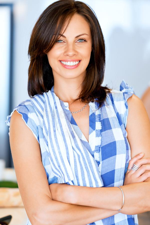 Ung kvinna som ler att stå med kökshandduken arkivfoton