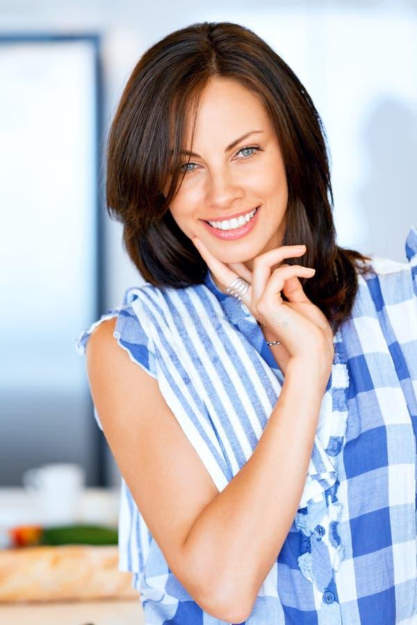 Ung kvinna som ler att stå med kökshandduken arkivfoto