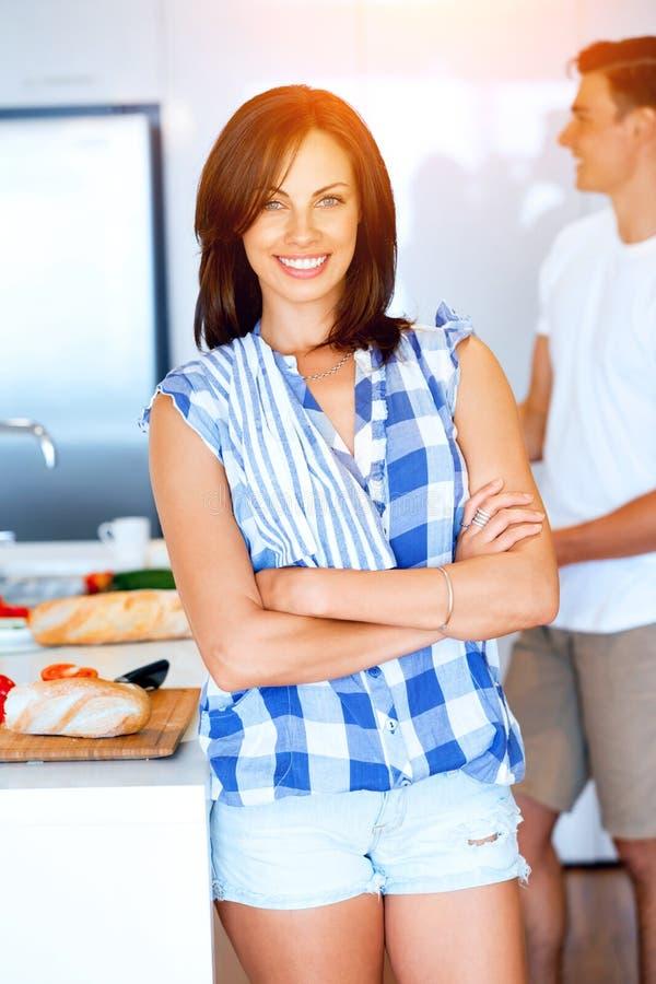 Ung kvinna som ler att stå med kökshandduken arkivbild