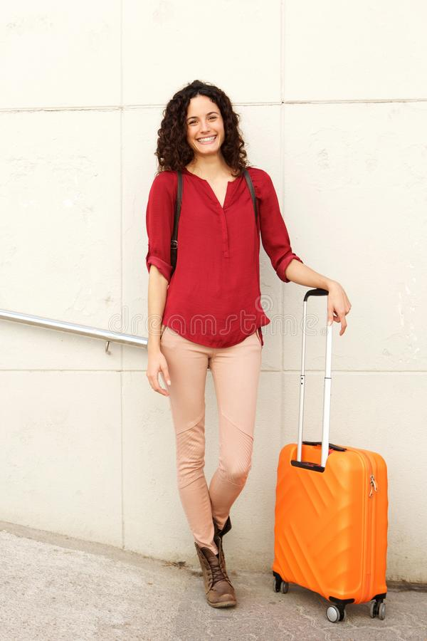 Ung kvinna som ler med resväskan mot väggen royaltyfri fotografi