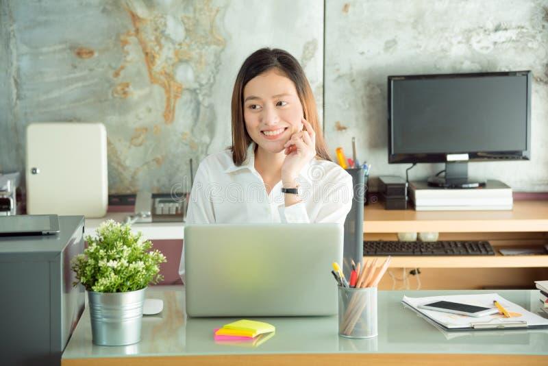 Ung kvinna som ler, medan arbeta det hemmastadda kontoret royaltyfria foton