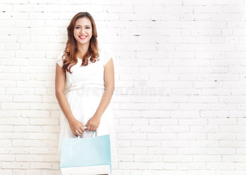 ung kvinna som ler, medan bära shoppingpåsar royaltyfria foton