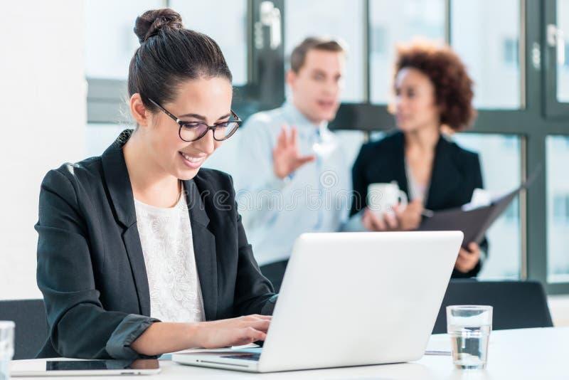 Ung kvinna som ler, medan genom att använda en bärbar dator i kontoret arkivbilder