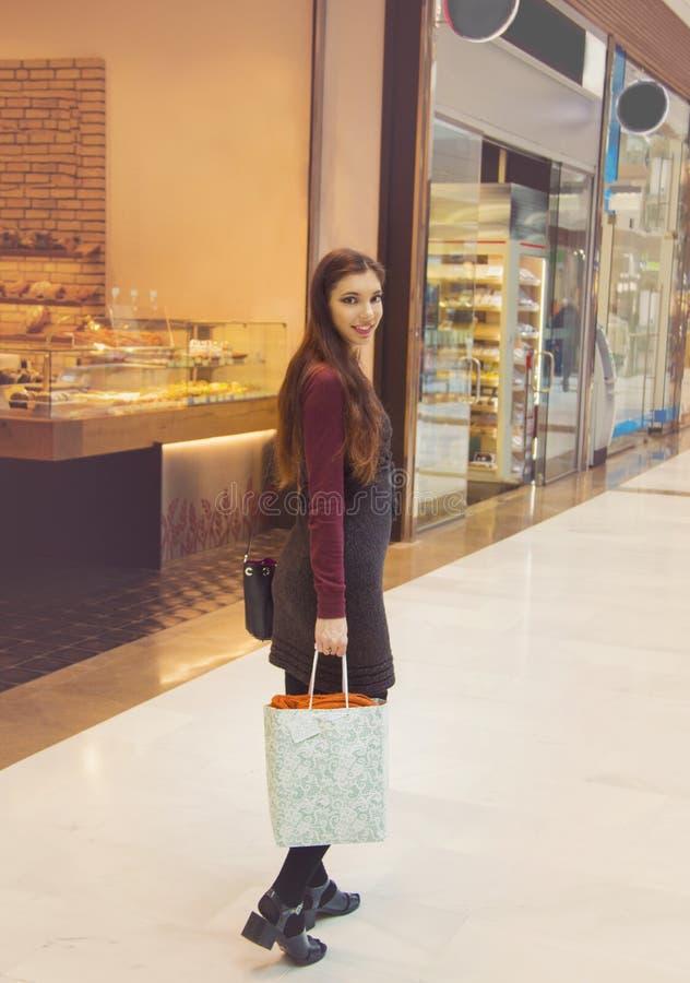 Ung kvinna som ler och rymmer shoppingpåsar som går i shoppinggallerian royaltyfri bild