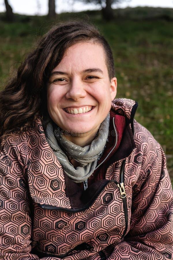 Ung kvinna som ler och tittar på kameran arkivbild