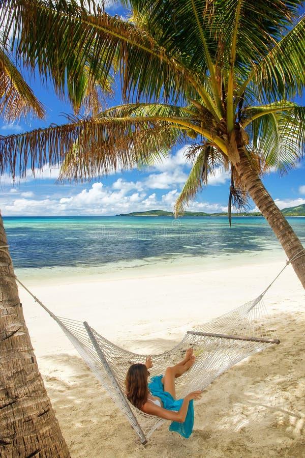 Ung kvinna som ligger i en hängmatta på en tropisk strand royaltyfria bilder