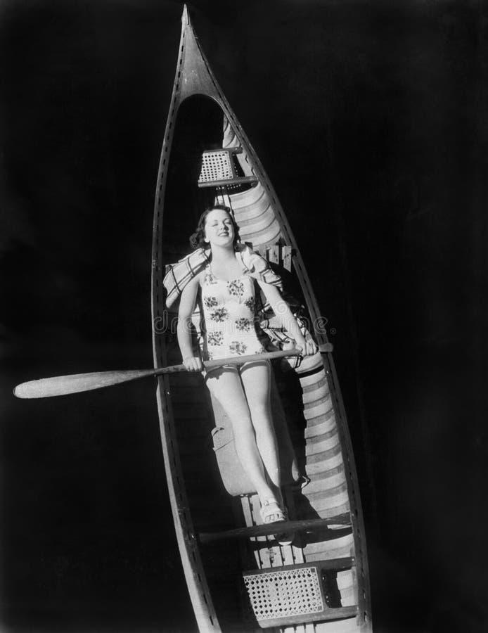 Ung kvinna som ligger i en kanot som solbadar, upp en liten vik med en skovel (alla visade personer inte är längre uppehälle och  arkivbild