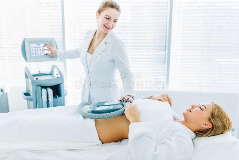 Ung kvinna som ligger i medicinsk soffa med att kyla beståndsdelar på buken i klinik royaltyfria bilder