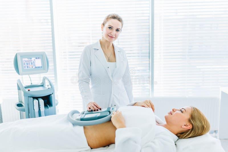 Ung kvinna som ligger i medicinsk soffa med att kyla beståndsdelar på buken i klinik royaltyfri bild
