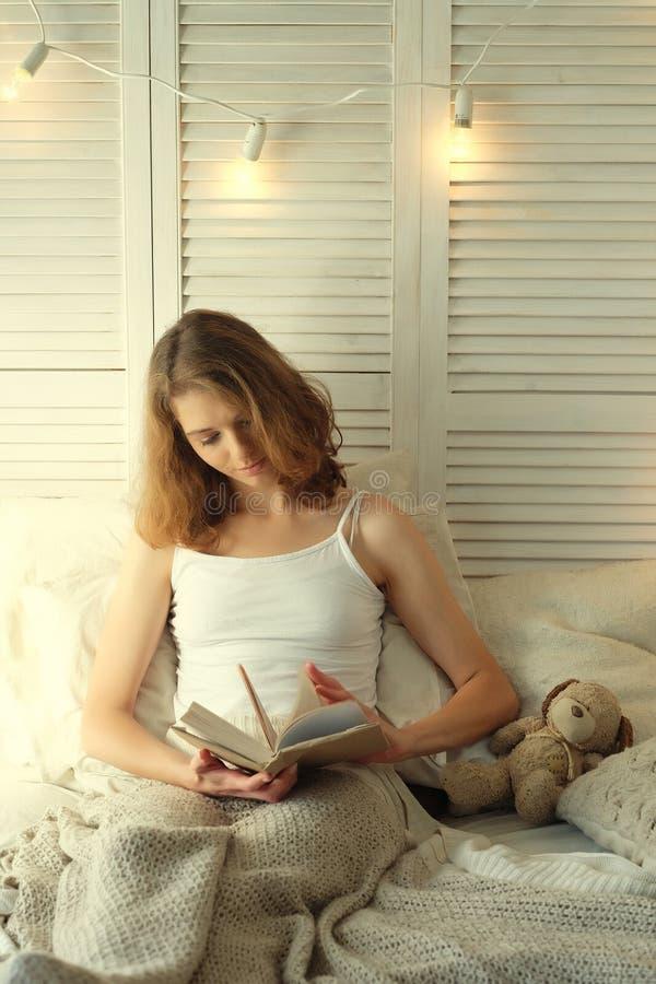 Ung kvinna som ligger i säng, medan läsa en bok royaltyfri fotografi