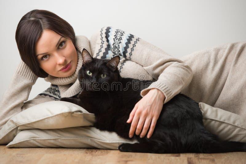 Ung kvinna som ligger med katten fotografering för bildbyråer