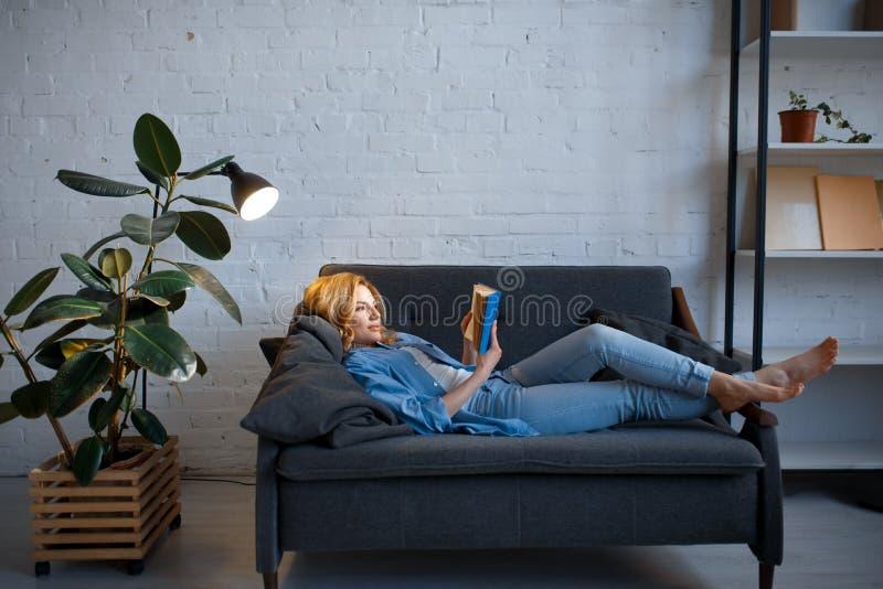 Ung kvinna som ligger p? den hemtrevliga soffan och l?ser en bok arkivfoto