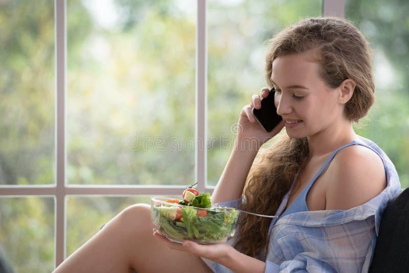 Ung kvinna som ligger på en soffa genom att använda smartphonen och innehavet en salladbunke royaltyfria foton