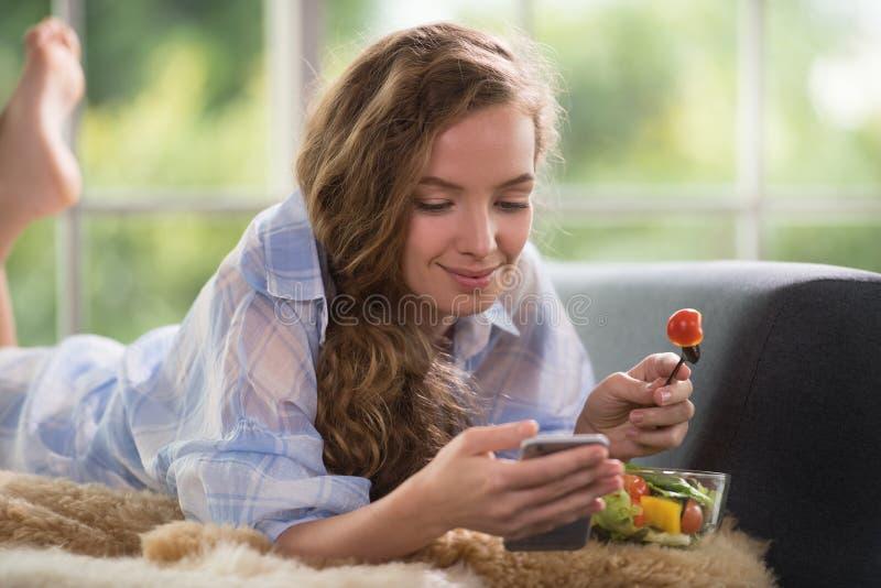 Ung kvinna som ligger på en soffa som rymmer en salladbunke arkivfoto