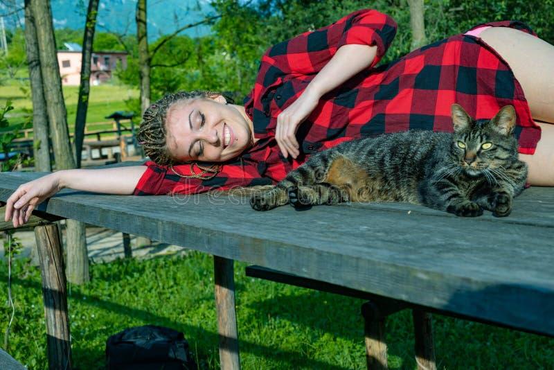 Ung kvinna som ligger på en tabell med hennes katt royaltyfri fotografi