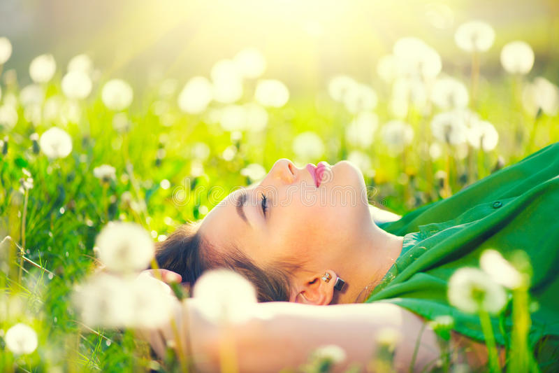 Ung kvinna som ligger på fältet i grönt gräs och maskrosor royaltyfri fotografi