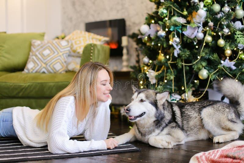 Ung kvinna som ligger på golv med den vuxna skrovliga near julgranen royaltyfri fotografi