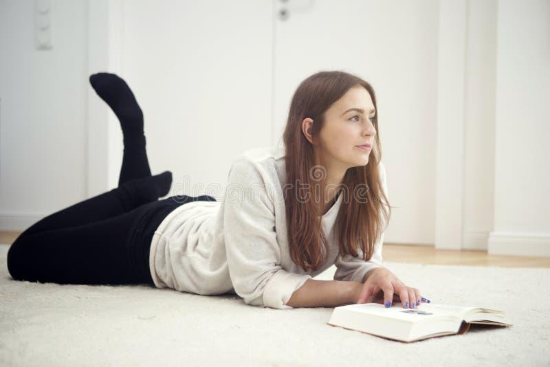 Ung kvinna som ligger på golv och läsning en bok royaltyfri fotografi