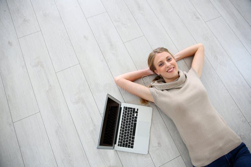 Ung kvinna som ligger på golvet med bärbara datorn royaltyfria bilder