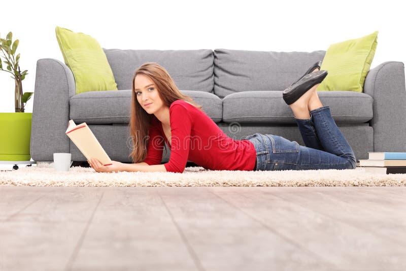 Ung kvinna som ligger på golvet och läsningen en bok royaltyfri bild