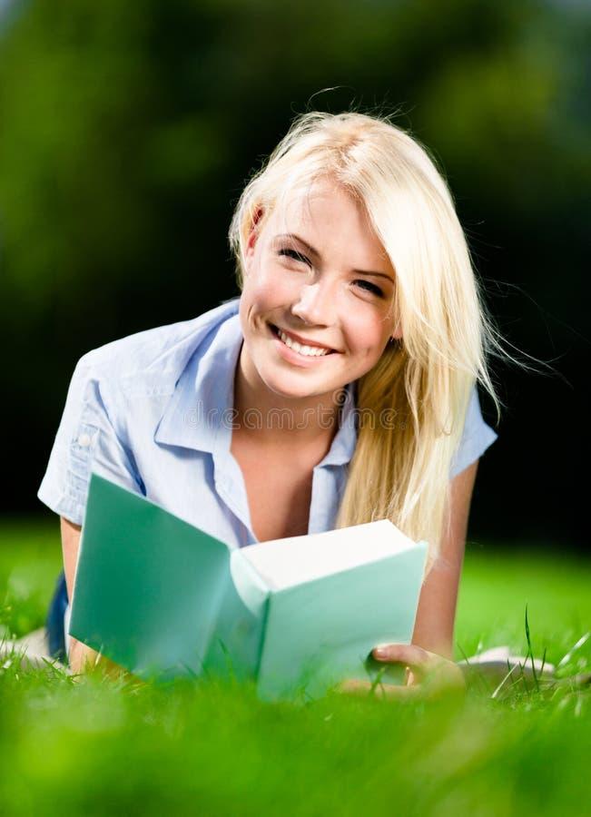 Ung kvinna som ligger på gräs med boken royaltyfri fotografi