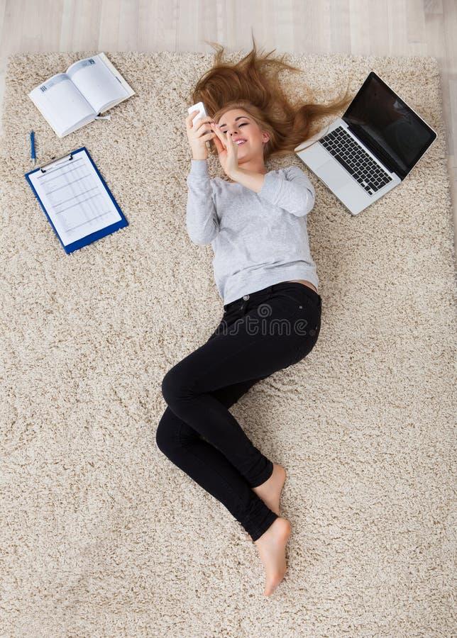 Ung kvinna som ligger på matta fotografering för bildbyråer