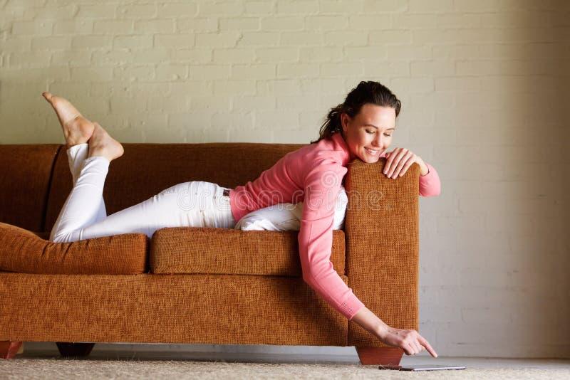 Ung kvinna som ligger på soffan genom att använda den digitala minnestavlan arkivfoton