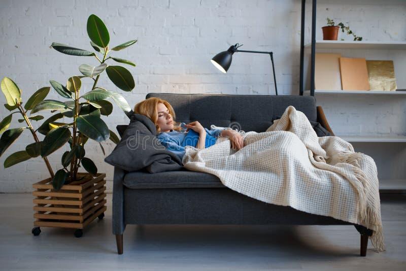 Ung kvinna som ligger p? den hemtrevliga soffan och l?ser en bok royaltyfri fotografi