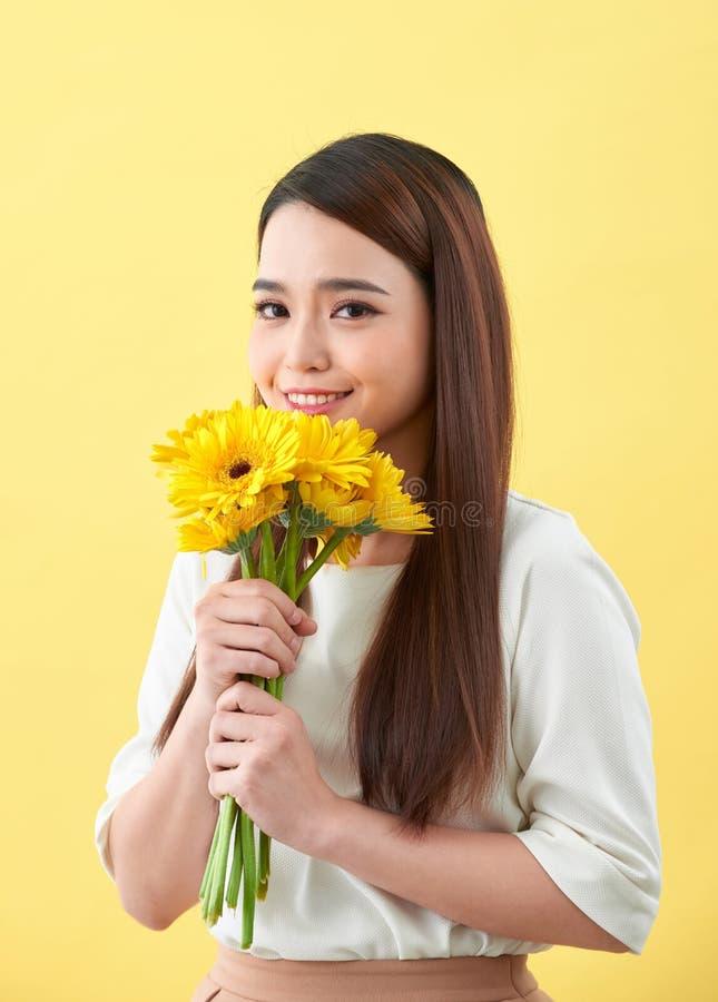 Ung kvinna som luktar solrosor p? den gula bakgrunden royaltyfria bilder