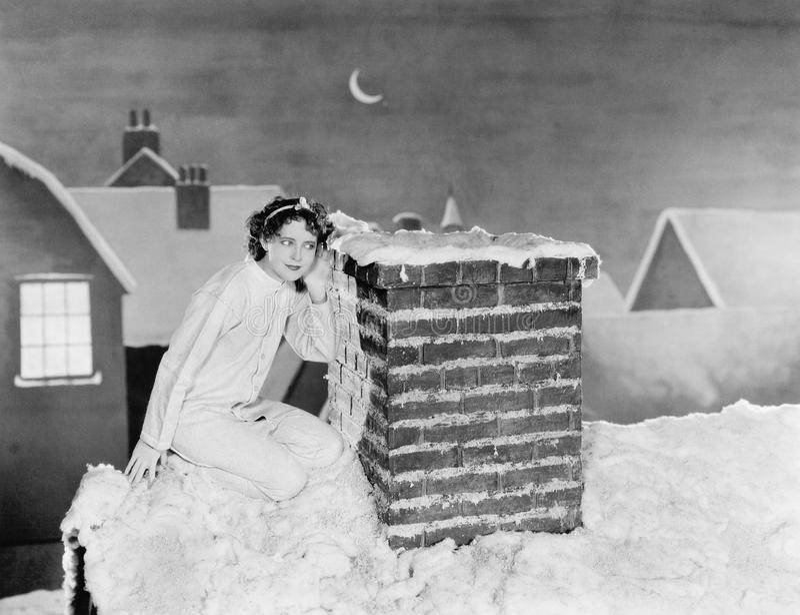 Ung kvinna som lyssnar på lampglaset på det snöig taket (alla visade personer inte är längre uppehälle, och inget gods finns Leve royaltyfri bild