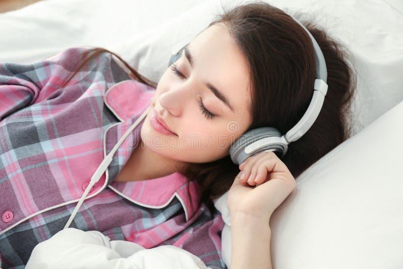 Ung kvinna som lyssnar till musik i hörlurar royaltyfri bild
