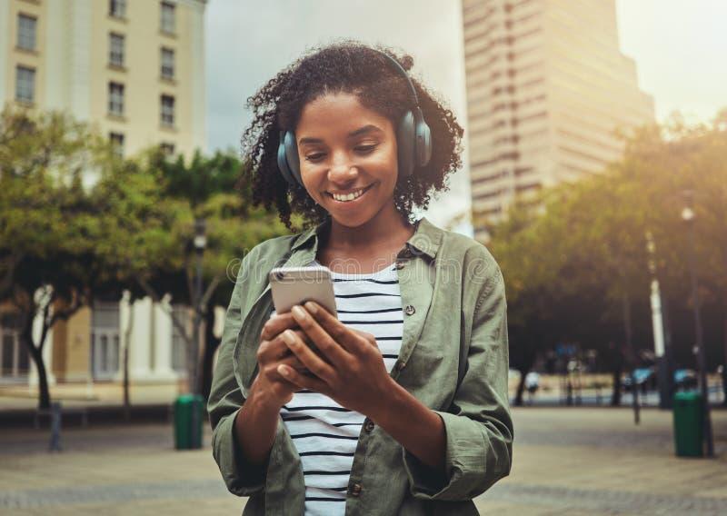 Ung kvinna som lyssnar till musiken fr?n en smart telefon royaltyfri fotografi