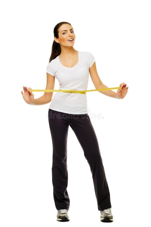 Ung kvinna som mäter henne waistline med ett mätande band över vit bakgrund royaltyfria foton