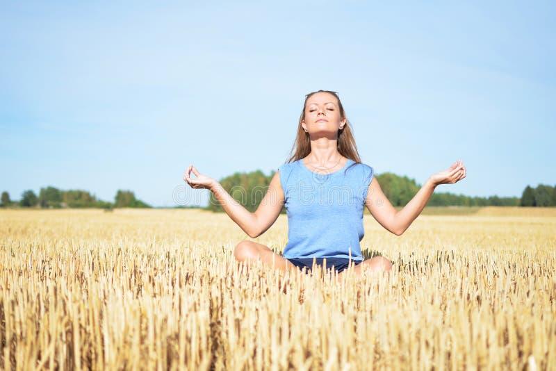 Ung kvinna som mediterar i fältet royaltyfri fotografi